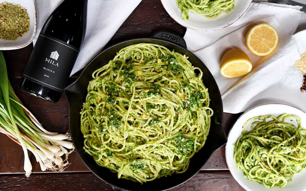 A pan of spaghetti with pesto next to a bunch of ramps (vegetables) and a bottle of Mila Block II Syrah wine.