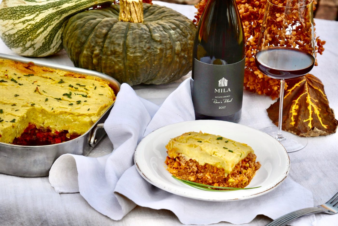 shepherd's pie on table with squash, wine
